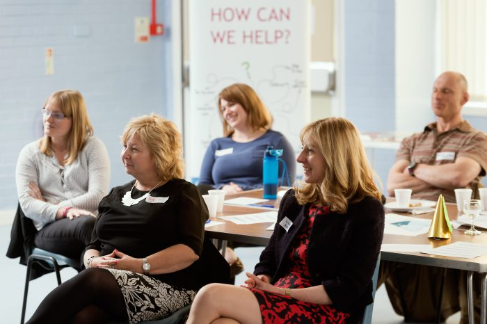 A group of educators watching a presentation at an information event