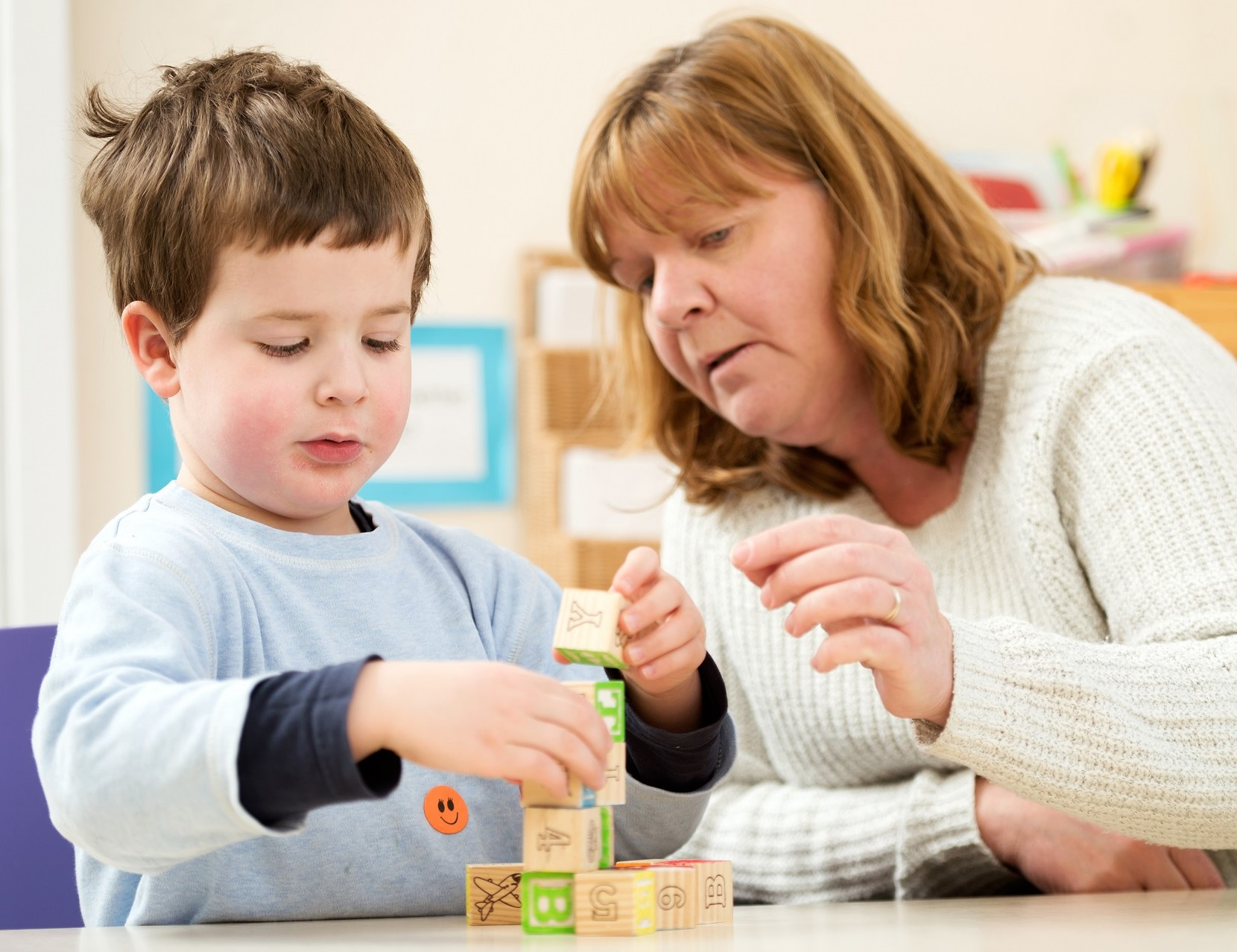 Dreghorn Pre-school and Creche pupil with teacher and building blocks