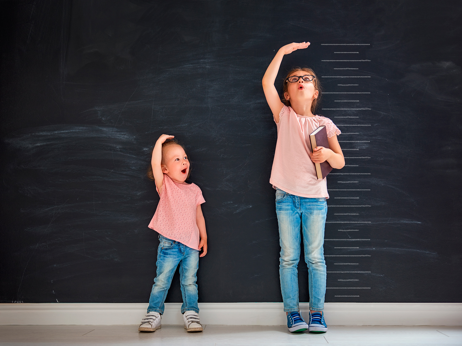 Little Girls checking their heights against a wall