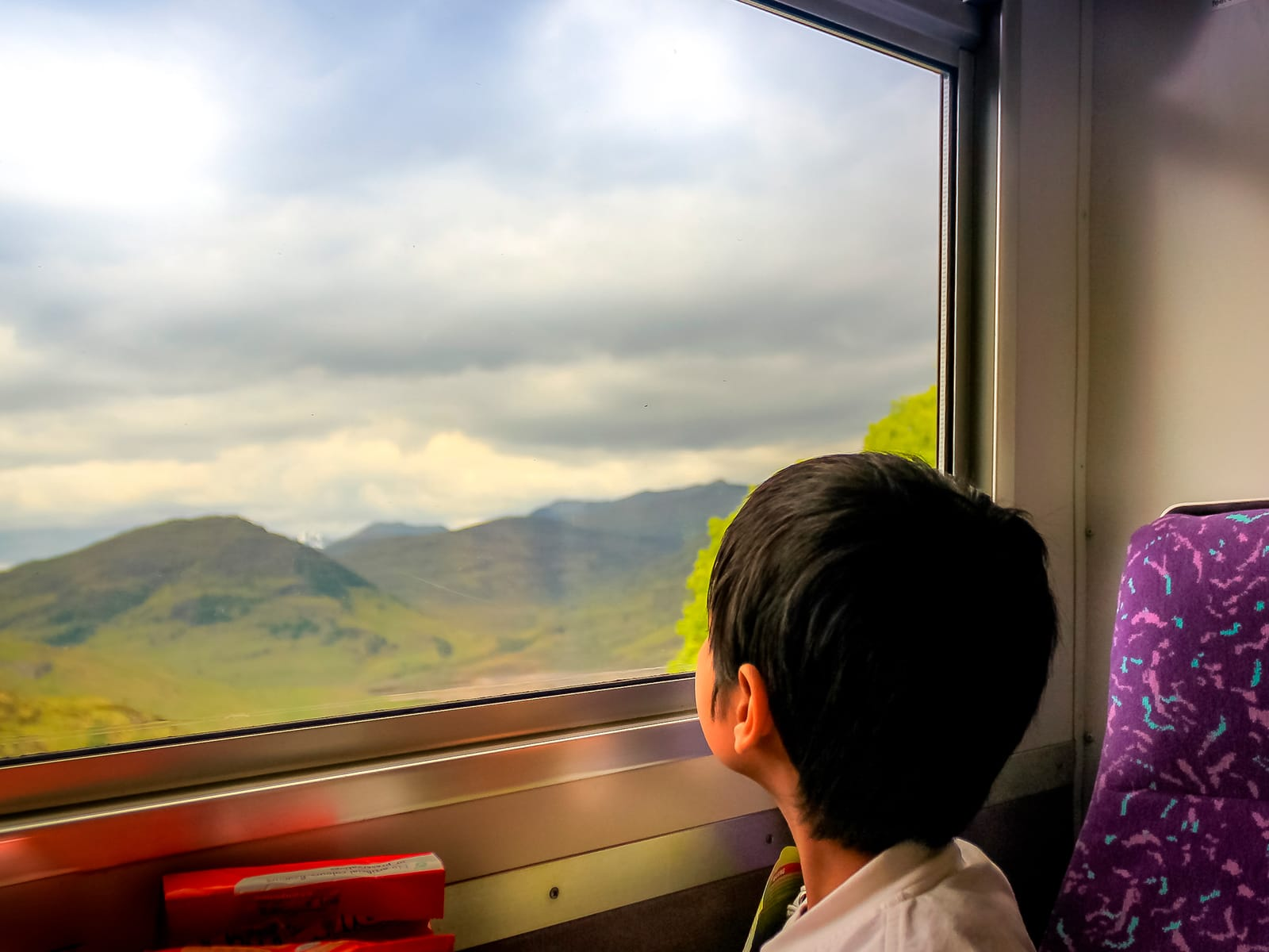 Young child looking out of a train window at the Scottish country side