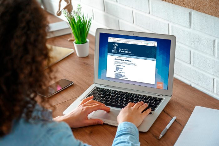 Woman with curly hair using the new Lanarkshire Firm Base website on a laptop