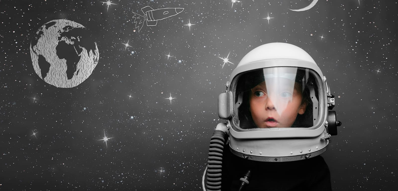 Child looking surprised in a retro styled space helmet
