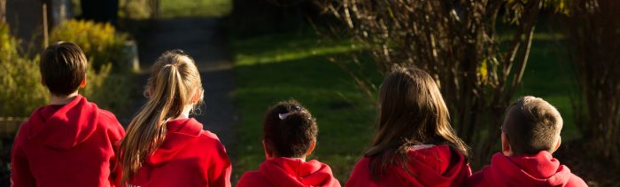 Children in red hoodies looking off in to the distance away from camera